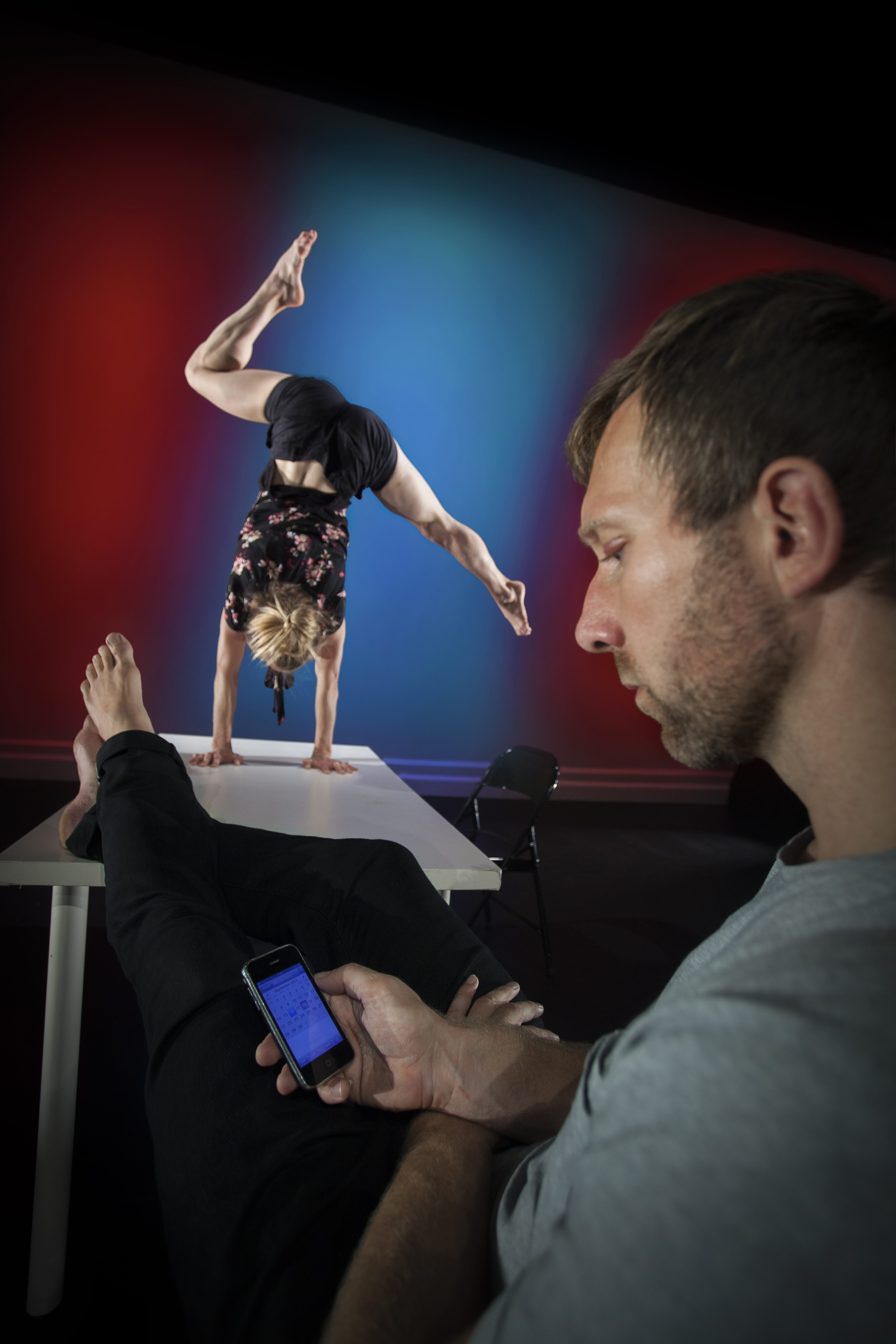 In the background, one dancer stands on her hands on a table, in the foreground a man stands staring at his mobile phone