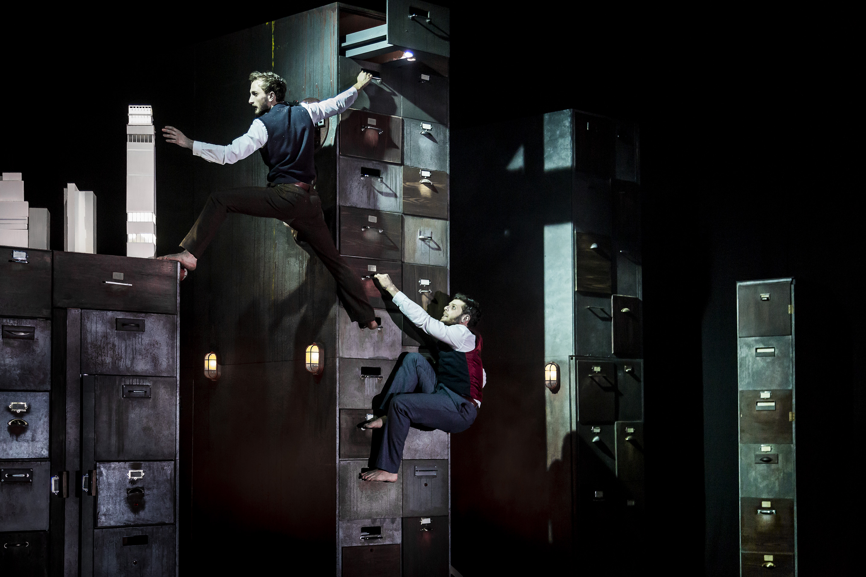 Actors climb fake filing cabinets as part of an elaborate set at Gecko Theatre.