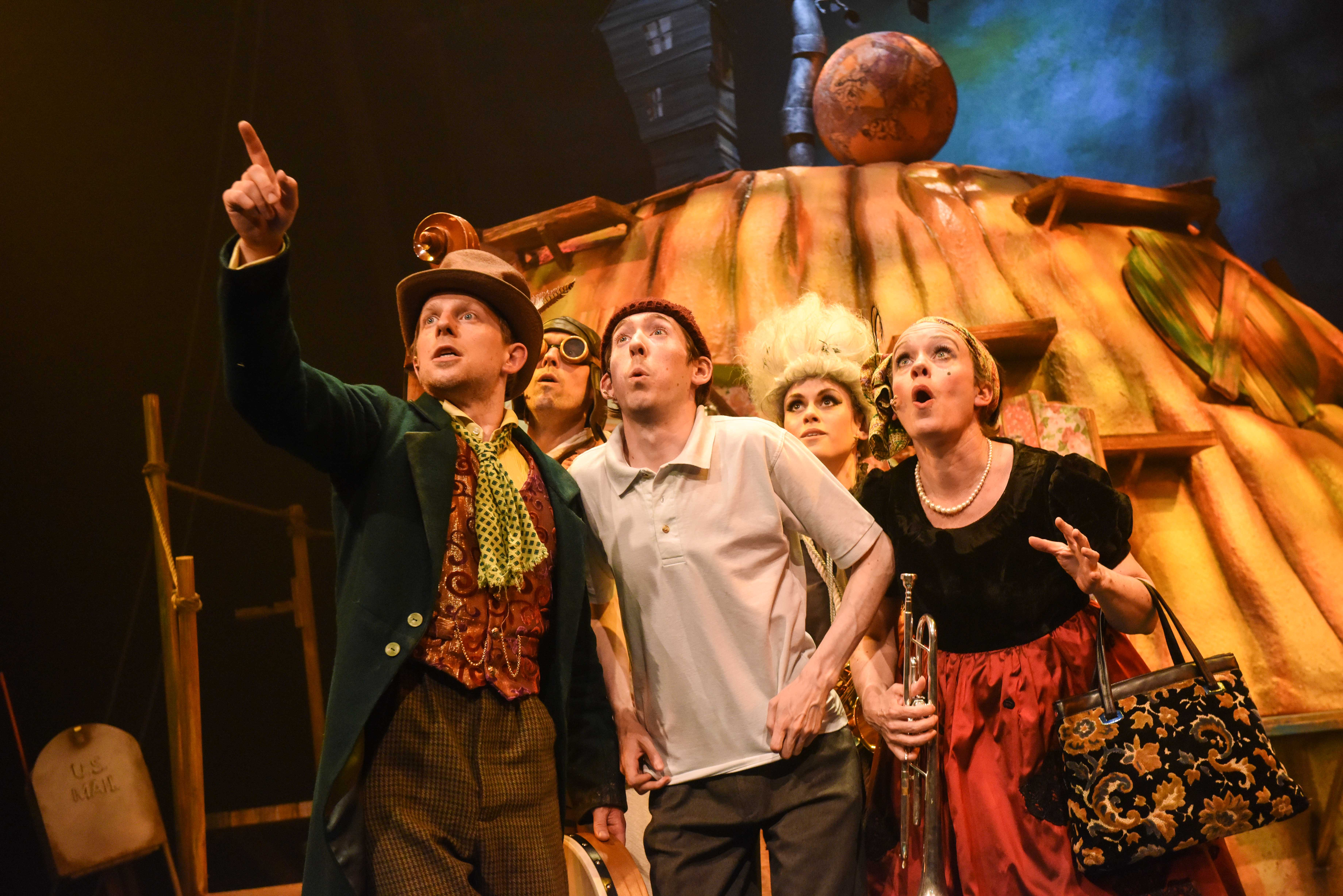Five actors on stage looking into the sky. They are standing in front of a giant peach.