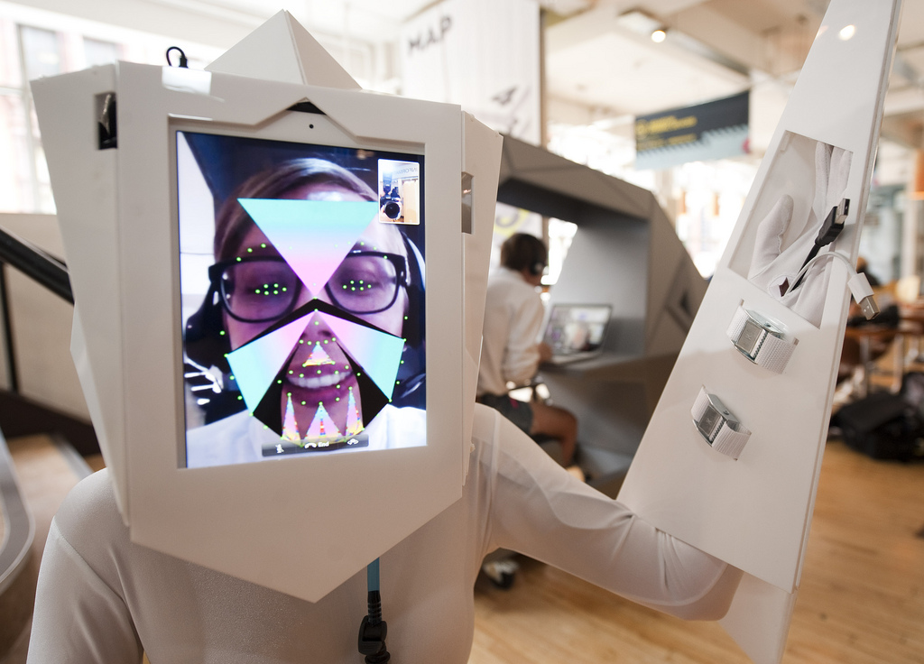 A lady wearing a white outfit augmented by a virtual reality helmet and gauntlet, with her face displayed on a digital screen overlayed with graphics in front of her actual face.