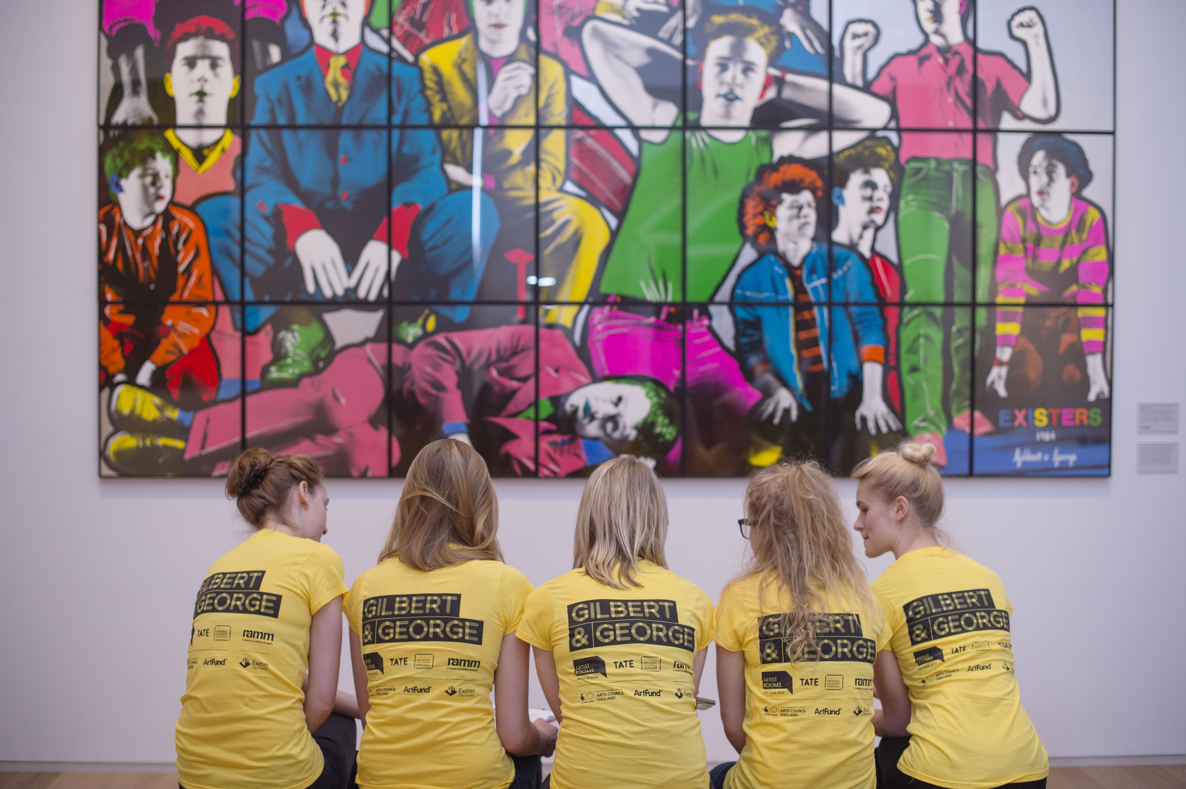 Volunteers in matching yellow T-shirts sitting on a bench facing away from onlooker, looking at Gilbert &George image on gallery wall
