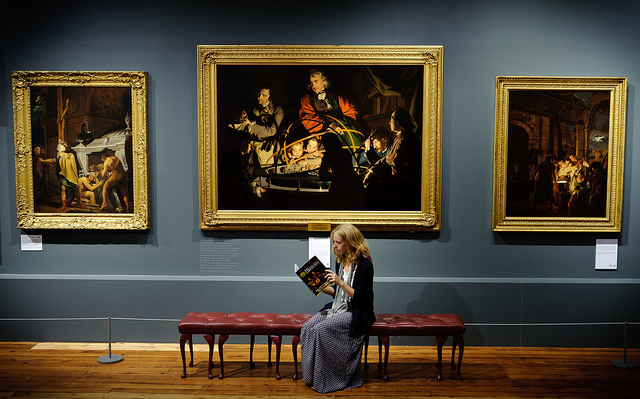 Lucy Bamford sits in front of the painting Joseph Wright's Orrery.
