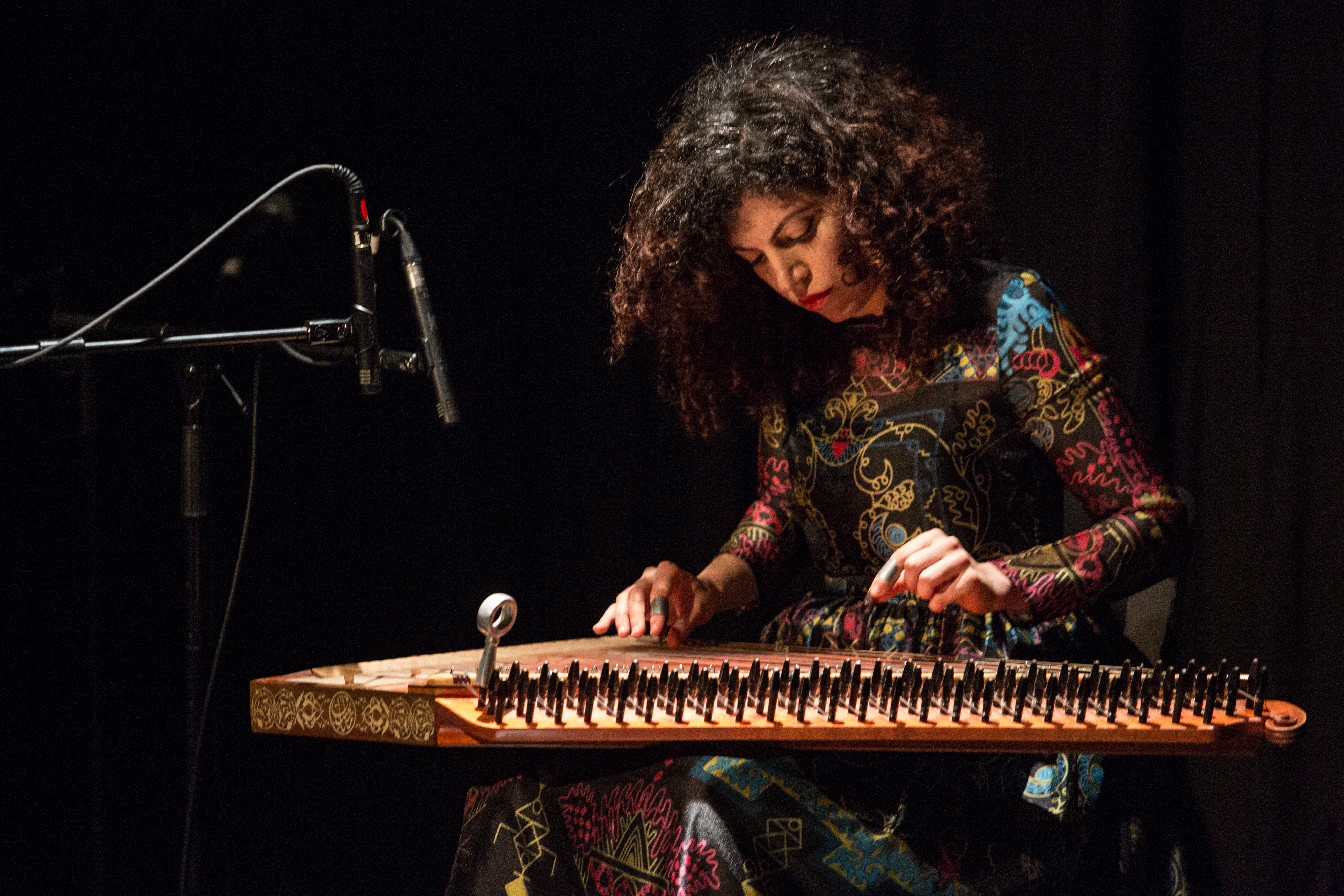 A musician plays a stringed instrument on her lap against a dark background