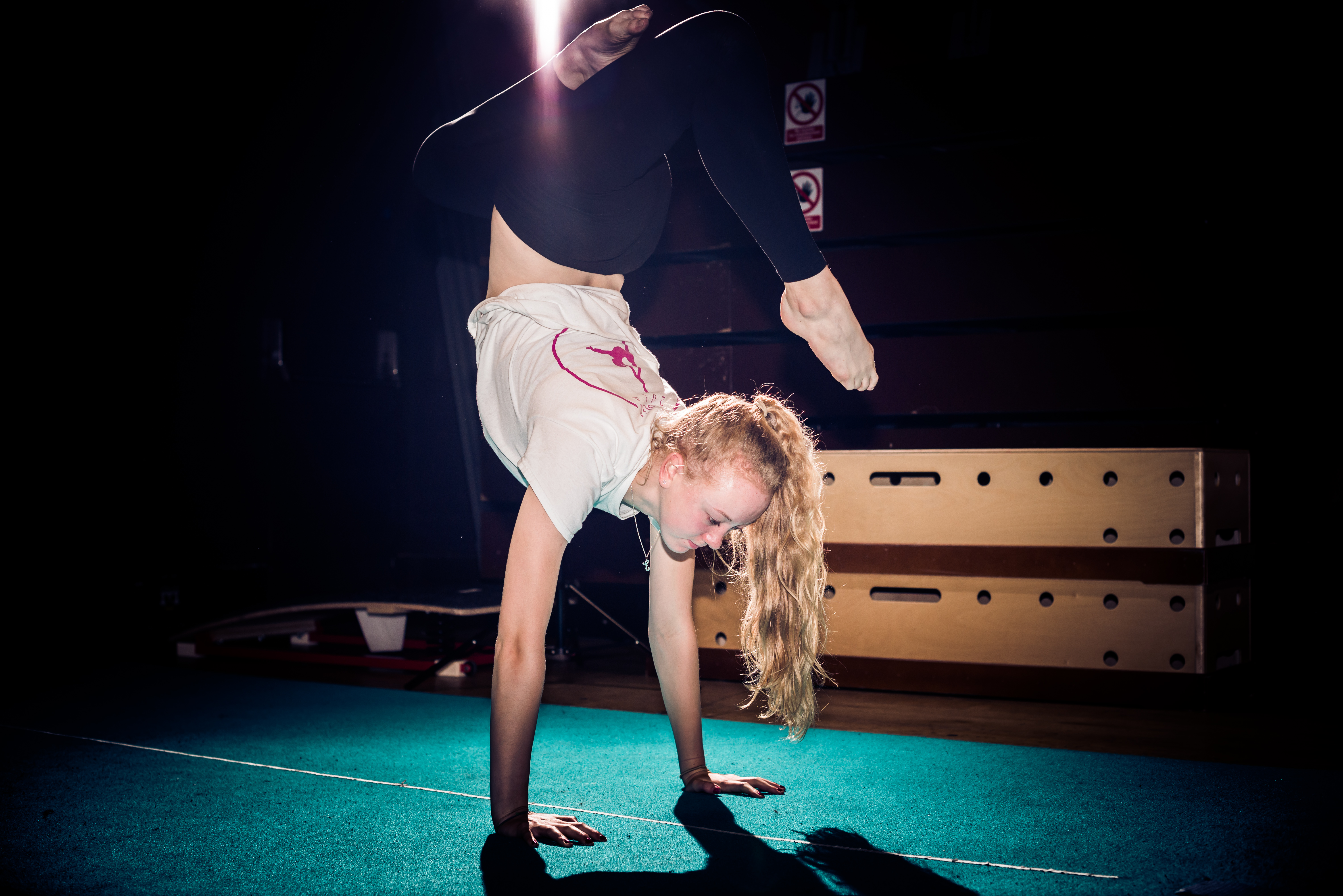 A young woman with long blonde hair performs a half handstand on a green mat