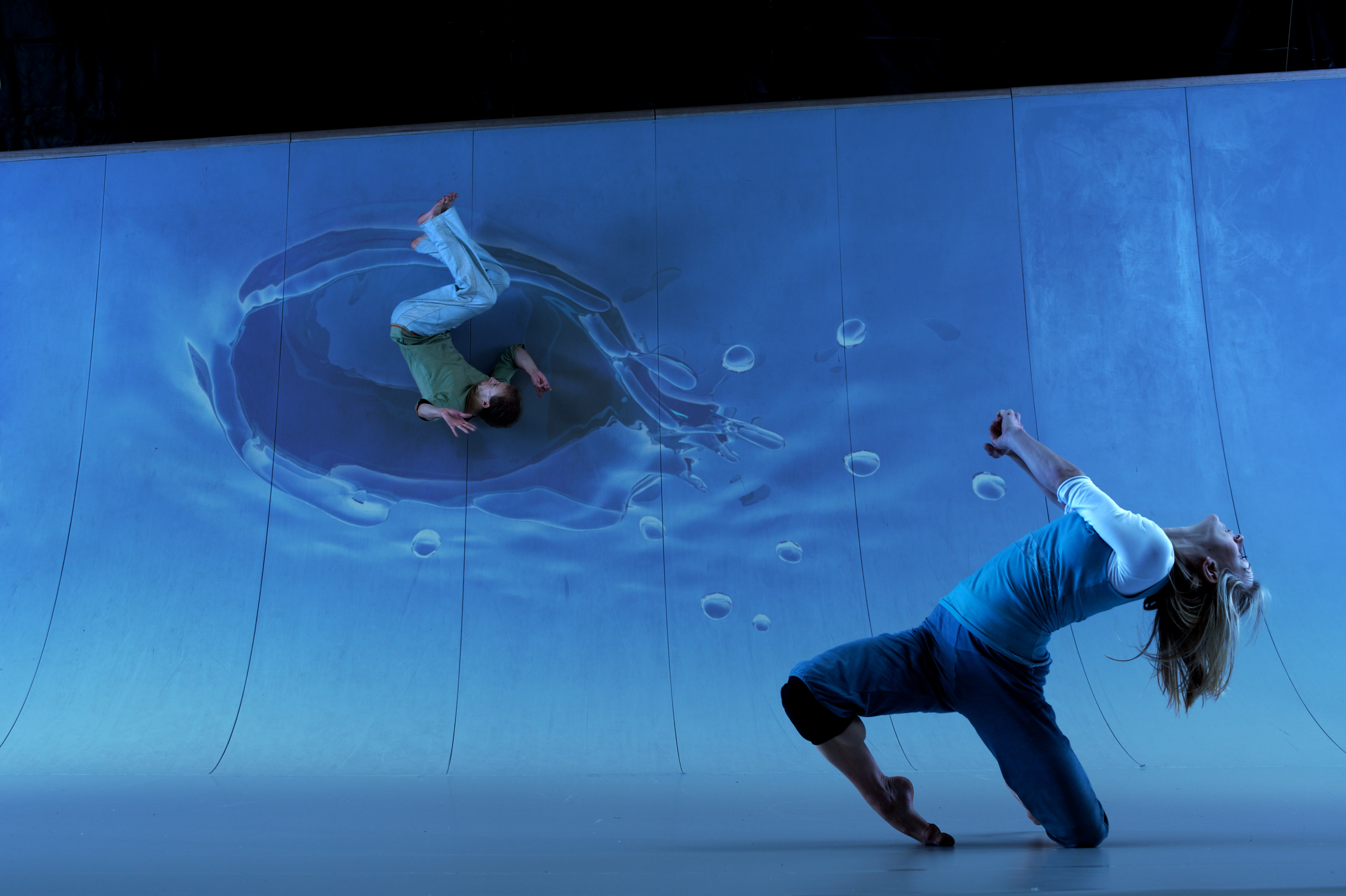 Two dancers from Motionhouse perform against a video backdrop, which features a water splash pattern where one performer appears to have hit the screen.