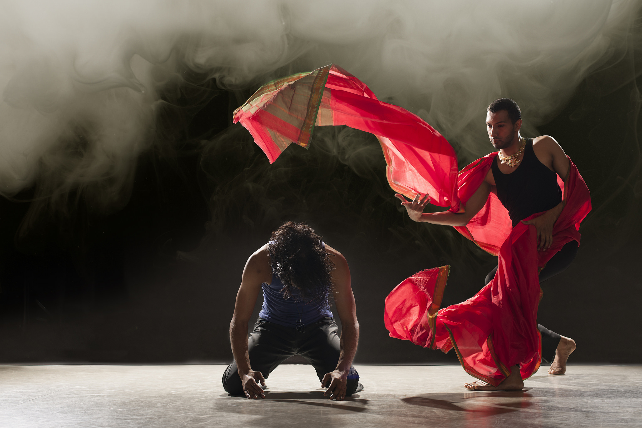 A dancer on his knees looks at the floor, while another dancer moves around him, a flowing red cloth blowing in the air within his grasp.