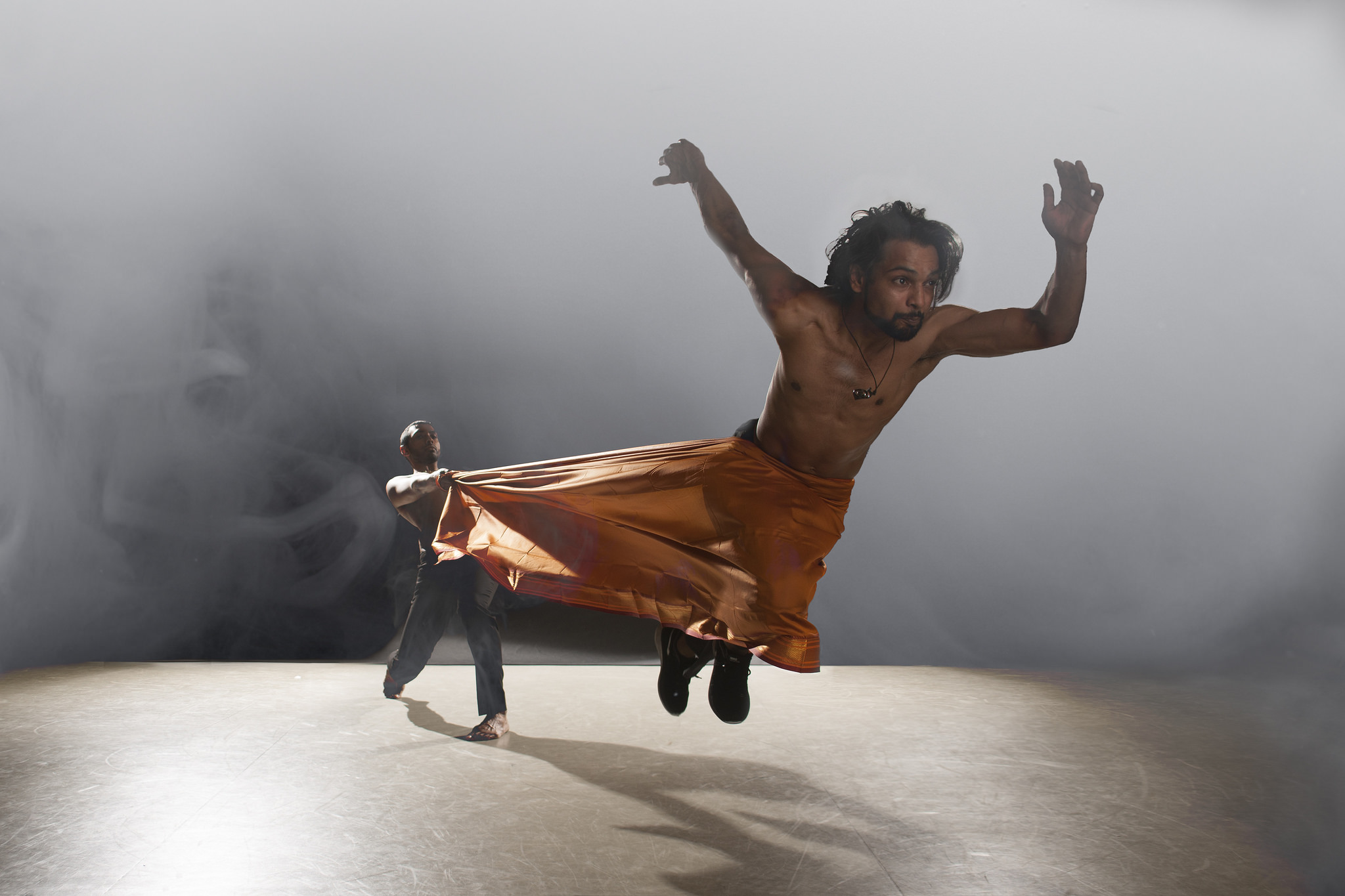 A dancer is hurled through the air, suspended by a large piece of fabric.