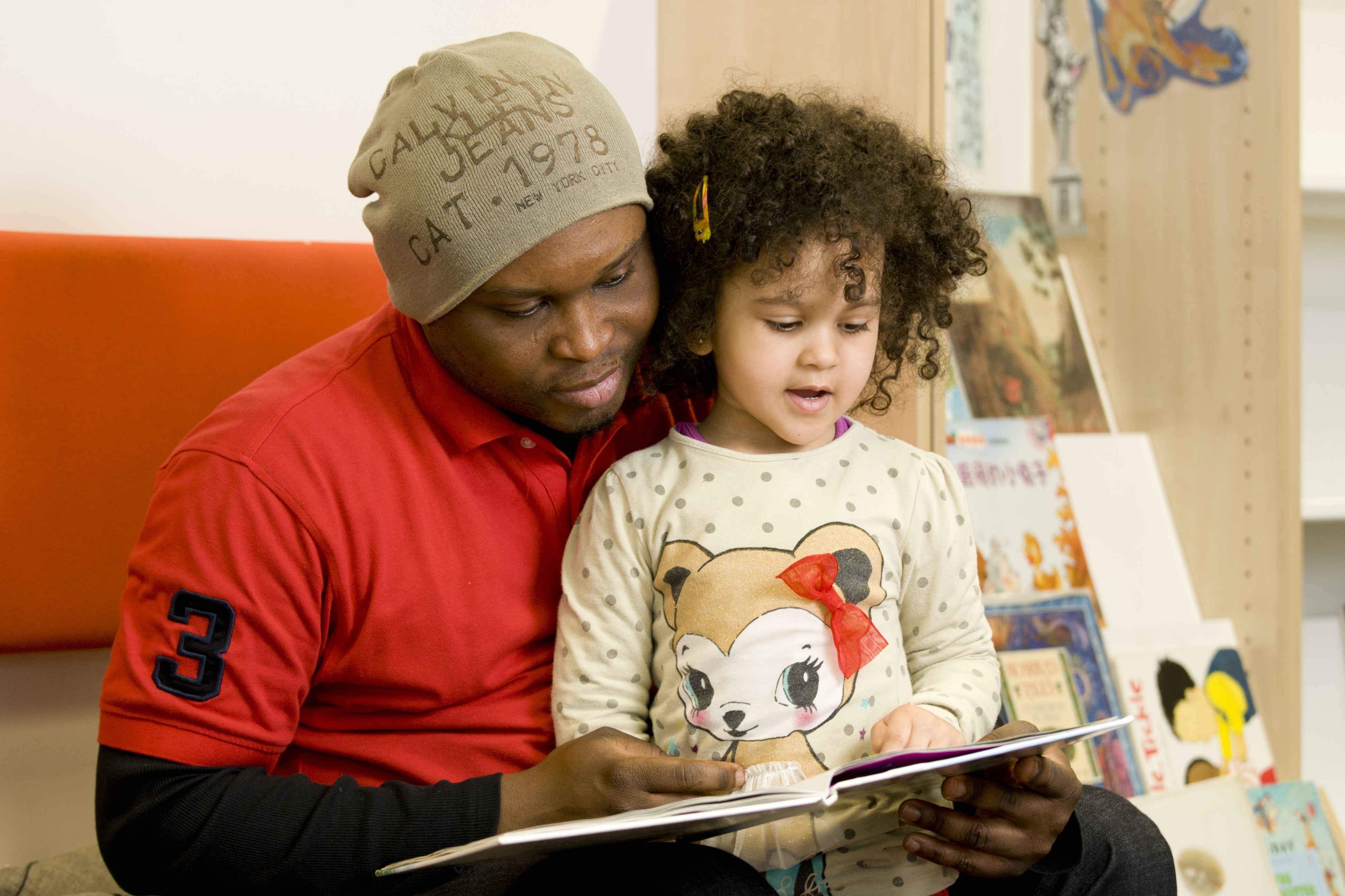 A young girl reads a storybook with a man.