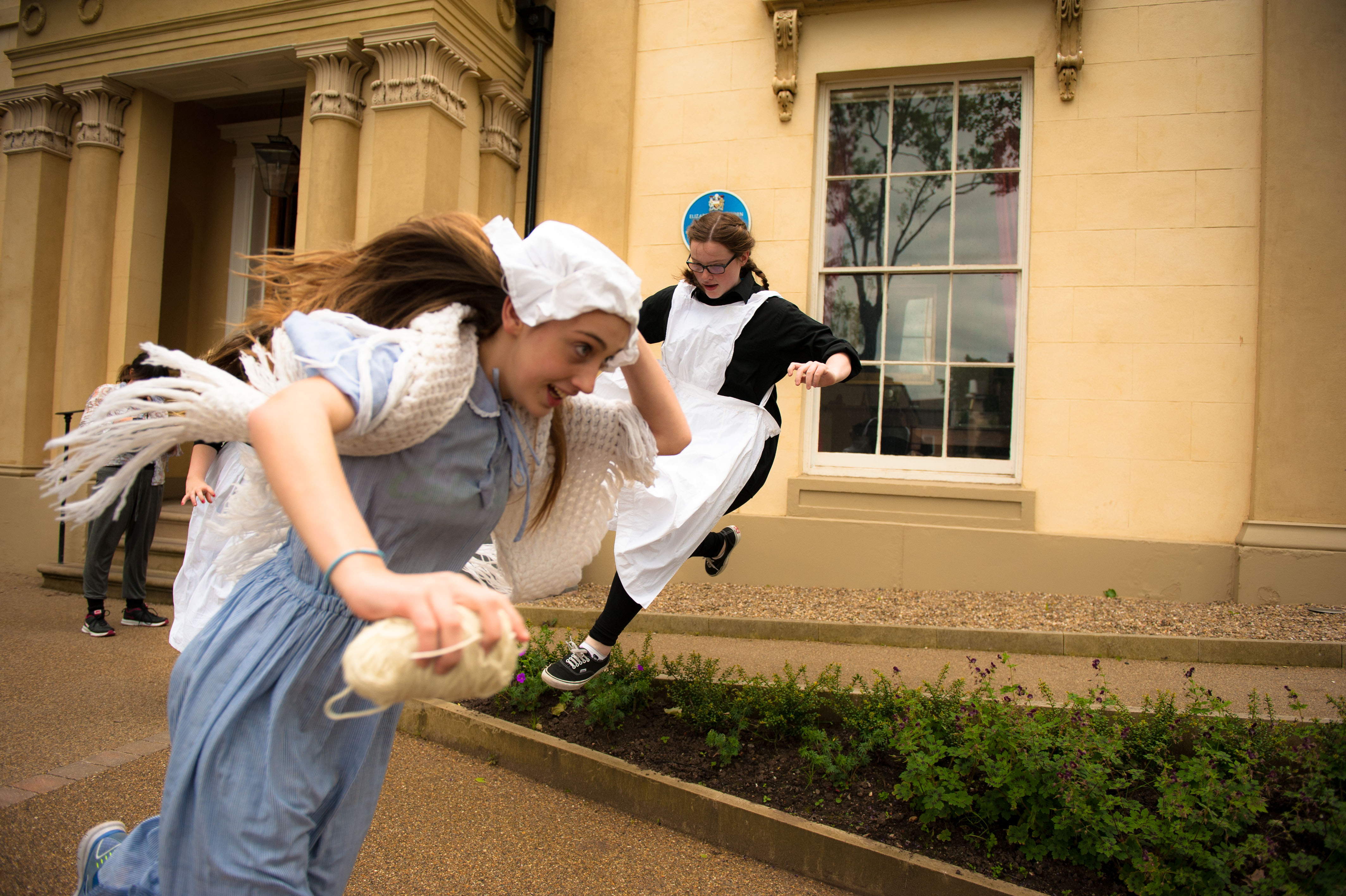 Two young women in maid dresses run outside of Elizabeth Gaskell House.