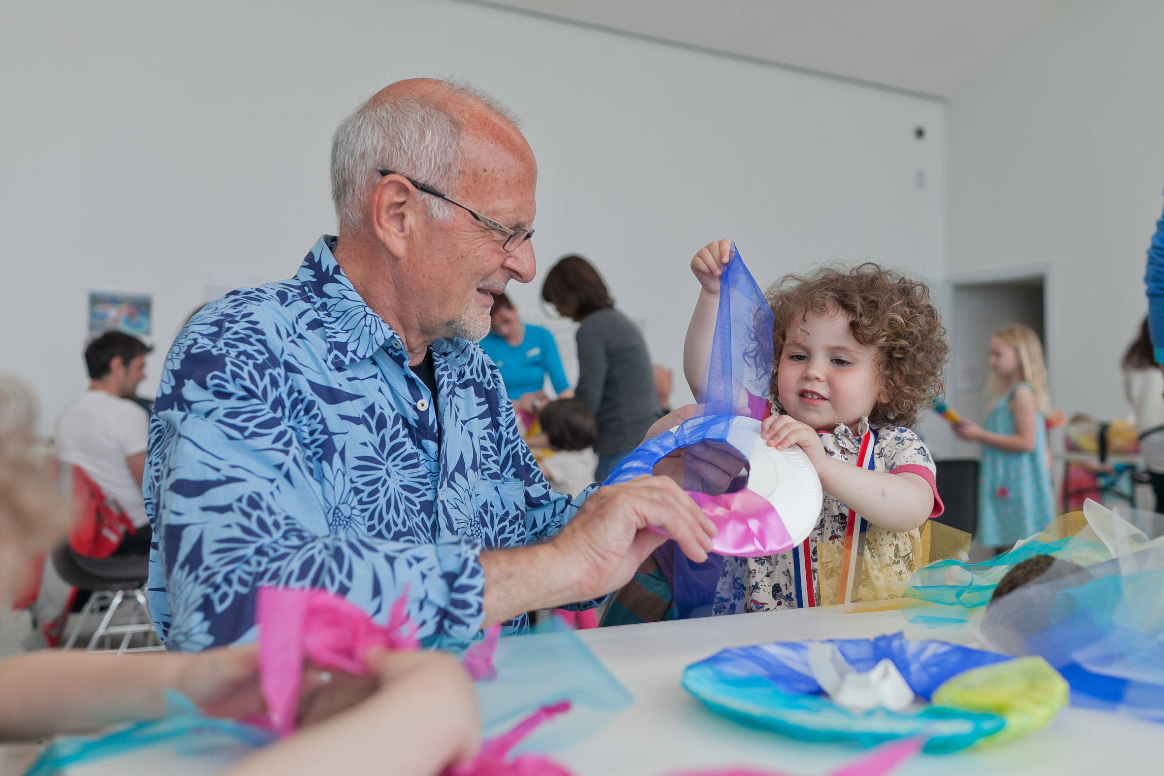 A young child and an elderly man make craft art together.