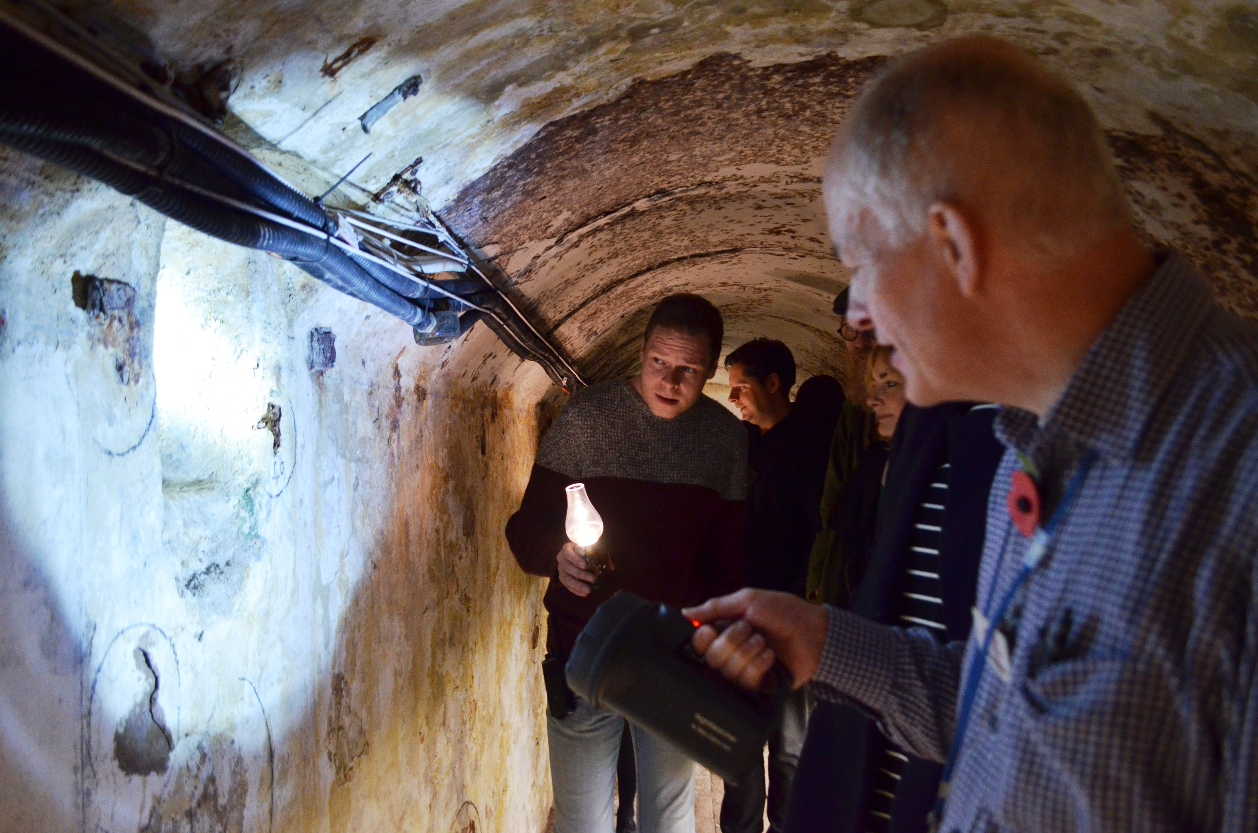 A tour guide shining a light on the wall whilst giving people a tour of the tunnels