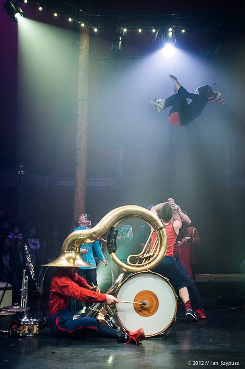 A man is sat on the floor playing a large drum, which is sat between his legs. A large brass horn (instrument) is sat on the top of the drum and the large end is covering the mans head. Acrobats are performing in the background, with one in the air.