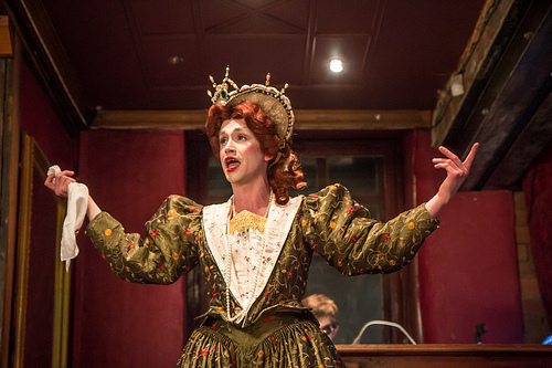 A male actor in drag Elizabethan costume delivers a speech with their arms outstretched
