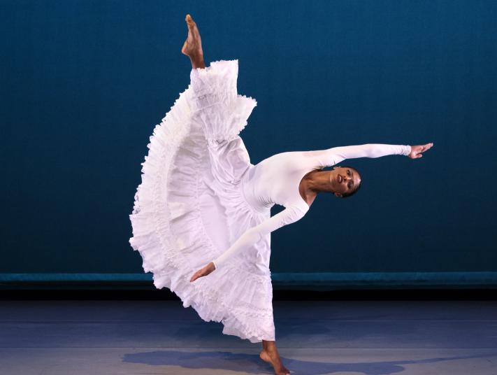 A dancer in a long white dress leans to the side with her leg stretched upwards