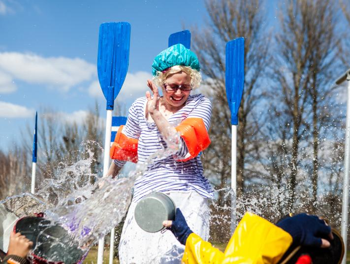 A woman in a showercap has buckets of water chucked over her.