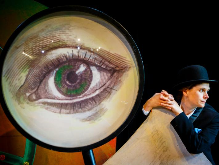 Lady in bowler hat leaning on cardboard whilst a giant hand drawn eye inside a magnifying glass looms behind her.