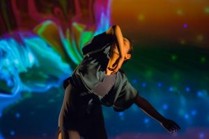 A dancer contorts in front of a screen showing a swirl of colours.